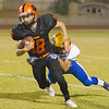 Woodlake Tiger WR Justin Hoskins (18) attempts to elude the tackle of  a Corcoran Panther defender. The Tigers scored a 28-27 homecoming game victory over their ESL rivals.
