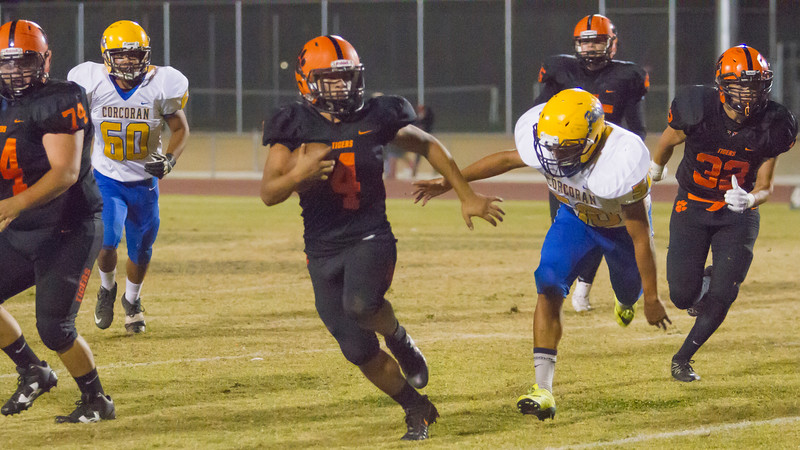 Woodlake RB Noe Garcia rushes through the line during the Tigers' 28-27 homecoming victory over the visiting Corcoran Panthers.