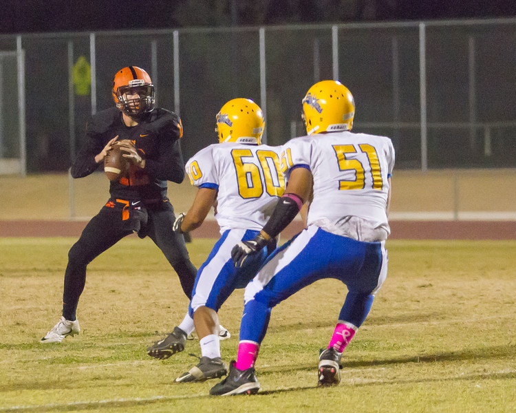 Woodlake QB Robert Stevenson (12) drops back to pass as Corcoran Panthers defenders pursue. Woodlake scored a 28-27 victory in ESL play.