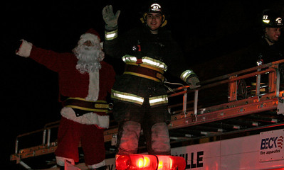 Santa Claus arrives at the Exeter Christmas parade atop an Exeter Fire truck.