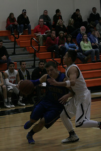 Exeter guard Aaron Coehlo (4) drives hard against Woodlake's Jaykob Velera in Tuesday's contest at Woodlake.