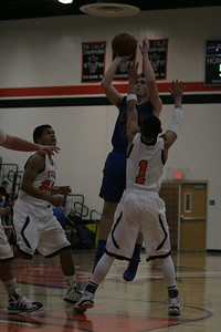 Exeter Monarch Aaron Coehlo shoots a jumper over Woodlake Tiger Jacob Velera in Tuesday's 73-43 victory.