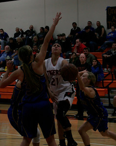 Woodlake's Kirsten Diaz  (21) drives for a lay up between Exter's Olivia Harden (33) and Jacqueline Hutcheson (2) during Woodlake's 43-37 victory.