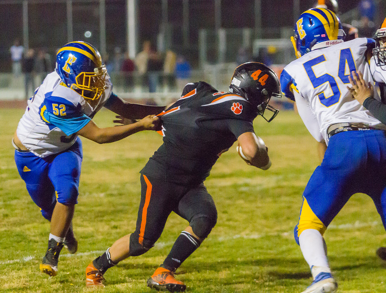 Exeter Monarch DT Abel Gonzalez grabs a hand full of the jersey of Woodlake Tiger RB Saul Palomo in CIF Division 5 playoff action. Exeter would defeat the Tigers 17-12 to advance.
