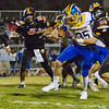 Exeter Monarch QB Jake Rowlett tries to escape Woodlake Tiger defender Kyle Davis (33) in CIF Division play. Exeter would defeat Woodlake by a 17-12 score to advance.