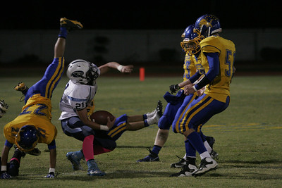 Exeter Monarch DB Joey Tobias (27) flips as he attempts to tackle Yosemite runningback Jason Lee (21).