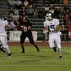 Farmersville Aztec runningback Joseph DeLaCruz (15) rushes the ball as Woodlakes Sam Palafox (50) pursues.