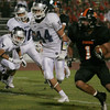 Woodlake's Elijah Cunningham rushes the football at Farmersville Aztec Edmund Winslow (44) pursues.