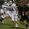 Woodlake's Elijah Cunningham rushes the football at Farmersville Aztec Edmund Winslow (44) pursues.