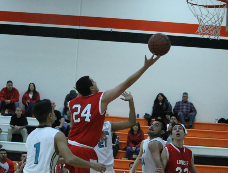 The Lindsay Cardinals played the Orange Cove Titans on Saturday, December 27th in the Frank Ainley Varsity Christmas Invitational Basketball tournament. Izaiah Diaz (24) drives the paint for a layup.