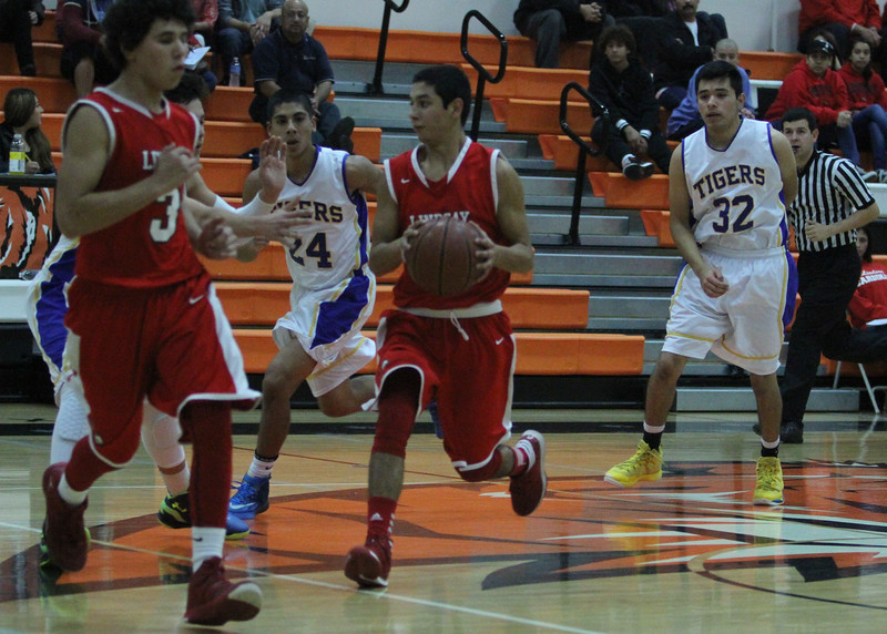 Lindsay Cardinal Guard R J Ruenda (1) brings the ball up court during action in the  Frank Ainley Christmas Invitational basketball tournament in Woodlake. The Cardinals lost a thriller to the Tranquillity Tigers 67-65 to finish 4th in the tournament that occurred during the winter recess.