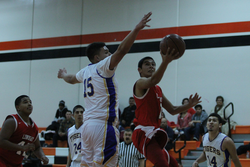 Lindsay Cardinal junior guard R J Ruenda (1) goes for a lay up against a Tranquillity defender in the recent Frank Ainley Christmas Invitational. The Cardinals dropped this contest 67-65 to finish 4th in the Woodlake tournament.