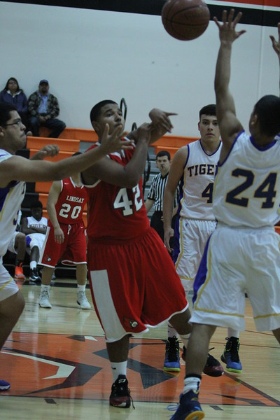 Lindsay forward Nate Sanchez (42) passes the ball away from several Tranquillity defenders during the Cardinal's recent Frank Ainley Christmas Invitational game. The Tranquillity Tigers overcame a 10-point halftime deficit to defeat the Cardinals 67-65.