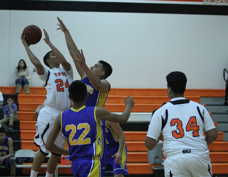 Woodlake lost a close contest against Tranquillity 54-50 on Saturday in the Frank Ainley Varsity Christmas Invitational basketball tournament. Woodlake Tiger Chris Garcia (24) shoots over a Tranquillity defender.