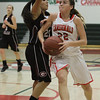 Cardinal Maddie Caesar (22) drives to the basket against Granite Hills Grizzlie Stephanie Aguilar. The visiting Grizzlies were able to defeat Lindsay 55 - 48 to hand the Cardinals their first league loss in 2 years.