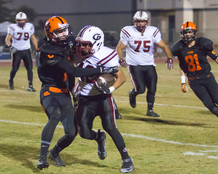 Woodlake Tiger DB Tell Blanke (8) tackles the Granite Hills ball carrier as Edward Munoz (82) pursues. The Tigers defeated the Grizzlies 14-6 in East Sequoia League play.