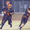 Woodlake Tiger RB Noe Garcia (4) rounds runs the ball up field with Tiger FB Victor Rojas (30) leading the way. Woodlake held on by a 14-6 score to win the annual Battle for the Belt game.