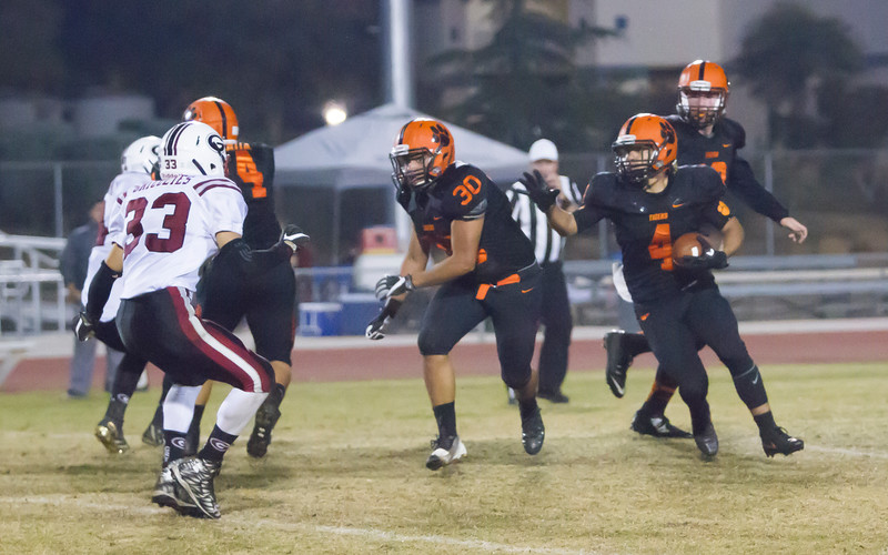 Woodlake RB Noe Garcia (4) waits for FB Victor Rojas (30) to put a hit on Granite Hills ILB Alexis Gil (33) during the Annual Battle for the Belt.<br /> Woodlake scored a 14-6 victory over the Grizzlies and will play Fowler High in the first round of the Division 5 Valley playoffs.