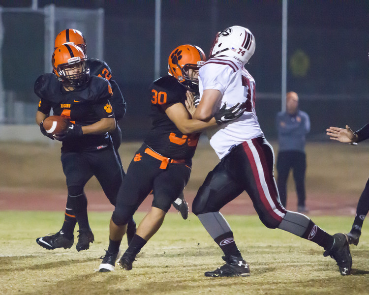 Woodlake Tiger FB Victor Rojas puts the block to a Granite Hills defender to spring RB Noe Garcia (4) for additional yardage. The Tigers defeated the Grizzles by a 14-6 score to advance to the Division 5 Valley playoffs.