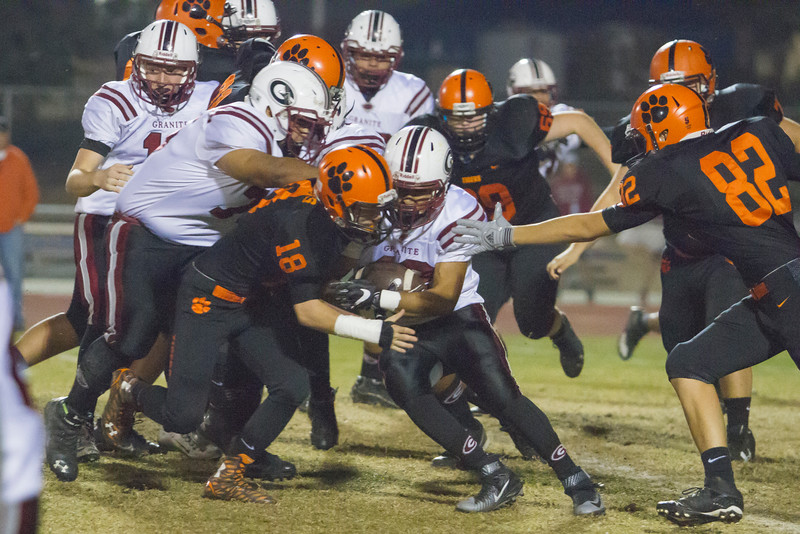 Woodlake Tiger Justin Hoskins (18) tackles a Granite Hills ball carrier during the annual Battle for the Belt rivalry game in Woodlake. The Tigers held on for a 14-6 victory. They will face Fowler High this week in the Division 5 playoffs.