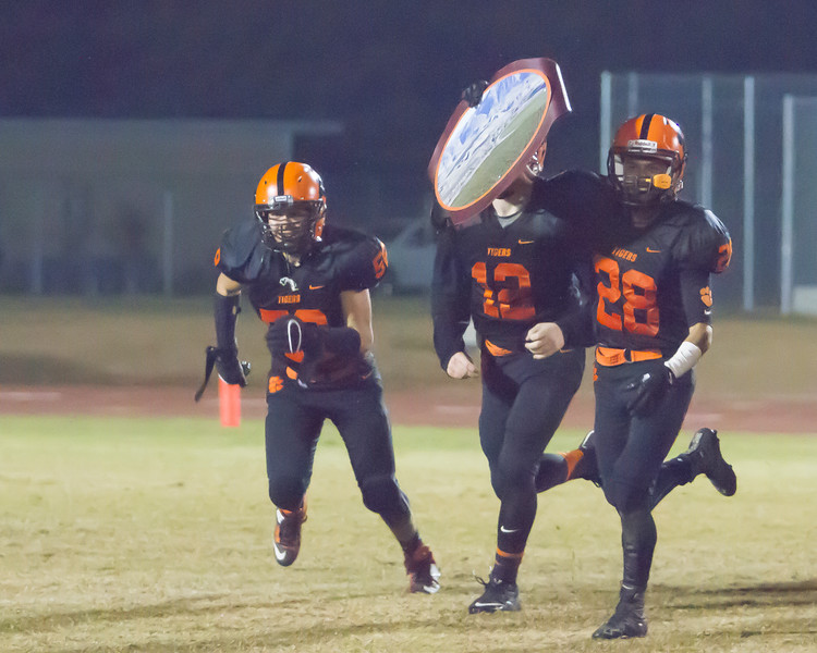 The Woodlake Tigers defeated the Granite Hills Grizzlies by a 14-6 score on Friday to win the Annual Battle for the Belt. Here Reyes Aguilar(52), Robert Stevenson (12), and Jordan Arce (28) run the Belt to the Woodlake student section.