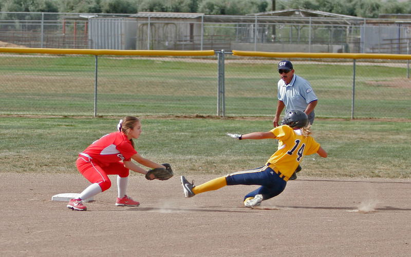 Lindsay Cardinal SS Lindsay Knutson gets set to tag Kern Valley outfielder Natalie Frias (14) during a steal attempt early in their quarterfinal game on Friday. Kern Valley scored 2 runs early and held off a 7th inning bases-loaded rally to advance.