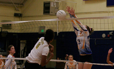 Exeter Monarch Allie Fry (3) blocks a spike by Kingsburg's Shawnice Sutton (8). Exeter won the match on Thursday 10-17 3-1.