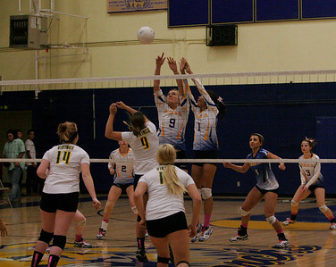 Exeter Monarchs Olivia Harden (9) and Amanda Acosta (1) attempt to block a spike by Kingsburg's Nicole Linman (9).