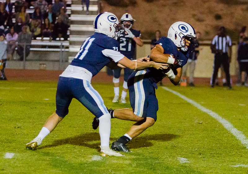 Central Valley Christian Cavalier QB Tyce Griswold (11) hands the football off to running back Jaalen Rening (4). The Cavaliers came up short against the undefeated Kingsburg Vikings by a 34-20 score.