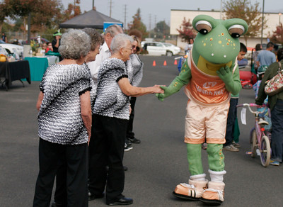 The Health Net Frog greats a group of senior citizen line dancers during the Lindsay Health & Fitness Fair.