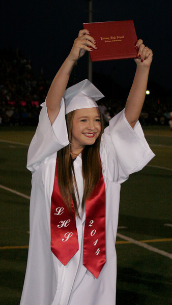 Linday High School graduate Marissa Knutson shows her diploma to friends and family during the 2014 Lindsay High School Commencement Ceremony.