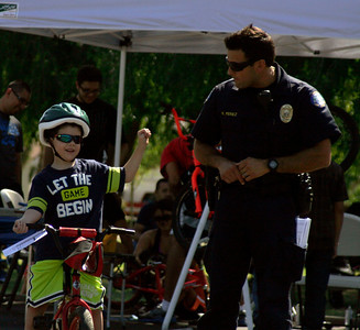 Jacob Thullen, age 6, shows Lindsay Officer Perez how to signal for a right turn at the Lindsay Kiwanis Bike Rodeo.