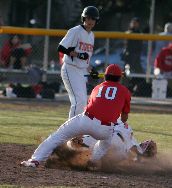 Lindsay relief pitcher Geovanni Perez attempts a tag a home on Woodlake's Sage Davis after a wild pitch during Woodlake's 13-2 victory over Lindsay on April 4th.