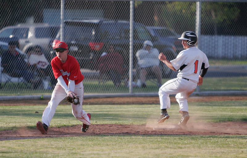 Woodlake's Zach Fesperman gets into 3rd base as Lindsay's Reeves Jacobs field the throw on a hop. Woodlake prevailed over Lindsay 13-2.