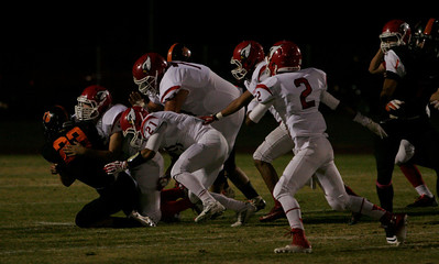 Woodlake Tiger running back John Kulick is tackled by a host of Lindsay Cardinals in the Tiger's