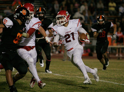 Jacob Hernandez (21) of Lindsay turns a run up field behind a block from Gaven Mann against Tiger Richard Hernandez (32)