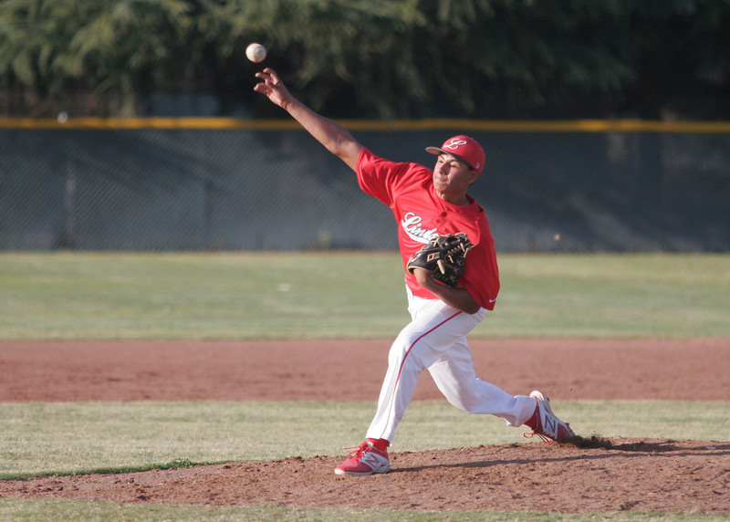 Lindsay Cardinal pitcher Israel Uribe lets a pitch fly against the Woodlake Tigers on Friday, March 21, 2014.