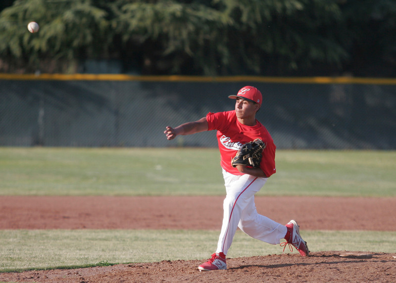 Lindsay pitcher Israel Uribe throws a pitch against Woodlake. The Tigers crushed the Cardinals 22-4.