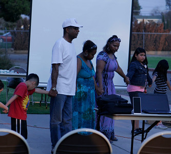 Pastor Loyd Johnson lead a circle of prayer to end gang violence during the MUAGA candlelight vigil on Saturday, March 16, 2013.