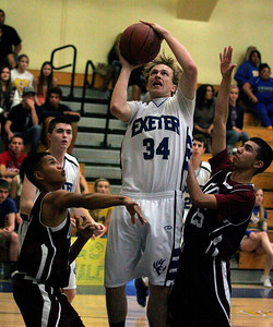 Exeter's Caleb Harden puts a rebound back up over two Orosi defenders during the Monarch's 63-43 playoff win over the Cardinals on February 25th.