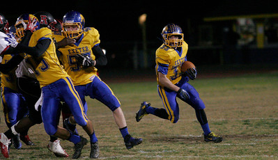 Exeter runningback Austin Cardoza (33) rounds the corner with blockers in front on his way to a touchdown.