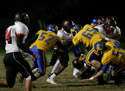Exeter defensive players Matt Valle (51), Huber Garcia (52), and Manson Grosvener (65) converge on Rosamond runningback Aldrick Olliver (10) early in Exeter's playoff game. Exeter 48, Rosamond 0.