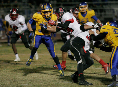 Exeter runningback Austin Cardoza breaks through the tackle of Rosamond LB Ricky Herrera. Cardoza had 84 yards on 13 carries.