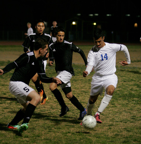 Exeter Monarch Chris Valvida (14) attempts to get around Sierra Pacific's Ignacio Rios during their Division VI playoff game. The Monarchs prevailed 3-2.