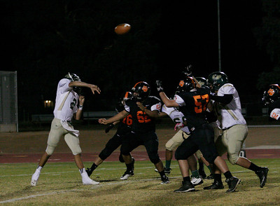 Sierra Pacific Quarterback Nicholas Moreno lets a pass fly as Forrest Cooer (76), Nick Negrete (62) and Juan Sandoval (57) rush the passer.