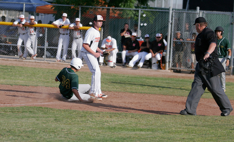 Sierra Pacific infielder Andrew Slater (34) scores on a pass ball as Woodlake pitcher Josh Bergdoll awaits a throw. Sierra Pacific beat Woodlake 4-0 to take the driver's seat for the EYL title.