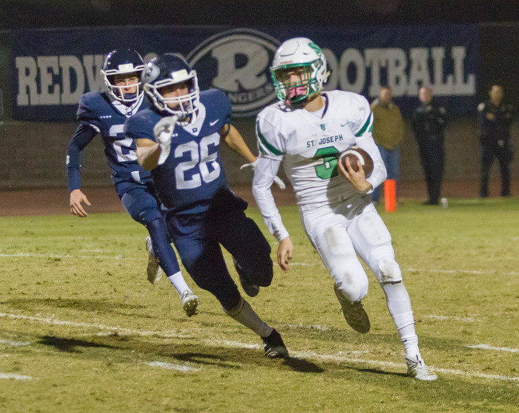 St. Joseph WR Darian Langley (3)  tries to escape the tackle of Redwood Ranger Caden Shafer (26) in Friday night CIF Cental Section D2 playoff action. The Knights would start fast and go on to win by a 28-21 score.