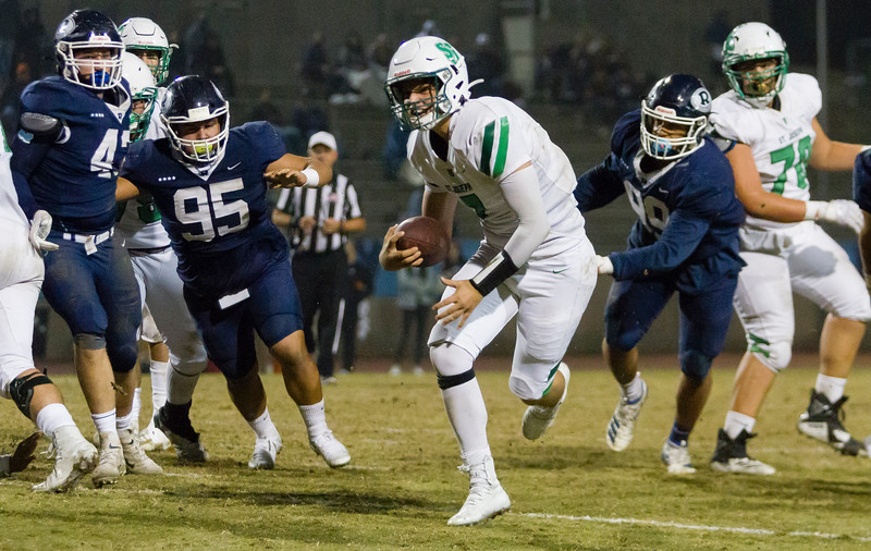 St. Joseph Knight QB Hunter Barnhart (7) gets by Redwood Ranger defenders Nathan Ibarra (95) and Marcus Garvey Correia (99) on a quarterback keeper. The Knights would go on to defeat the Rangers by a 28-21 score in CIF Central Section D2 playoff action.