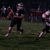 Farmersville quarterback Sam Metcalf (7) rolls out to evade the rush of Strathmore DE Grant Lockridge (6).
