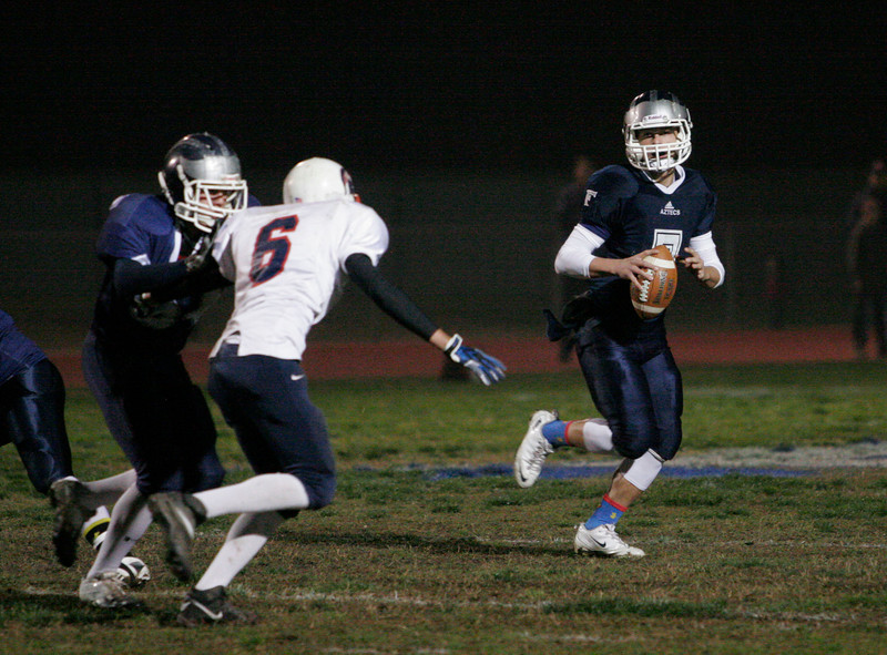 Farmersville Aztec quarterbck rolls out as Strathmore Spartan DE Grant Lockridge pursues. Metcalf was 20-31 for 372 yards and 5 touchdowns in the Aztec's win.